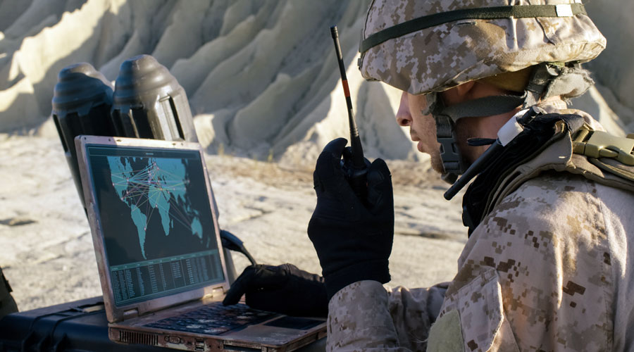 Soldier using laptop and radio for communication